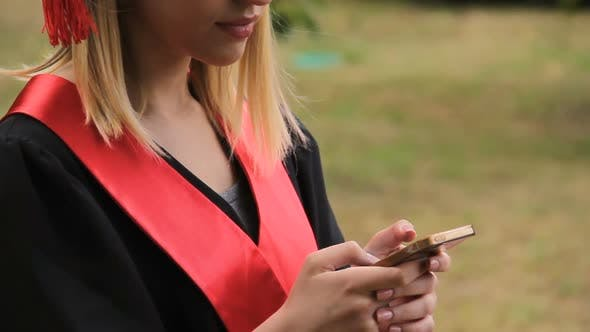 Cover Image for Beautiful Blond Graduate Texting on Smartphone After Graduation Ceremony