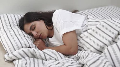 Lovely Woman Naps in Bed.
