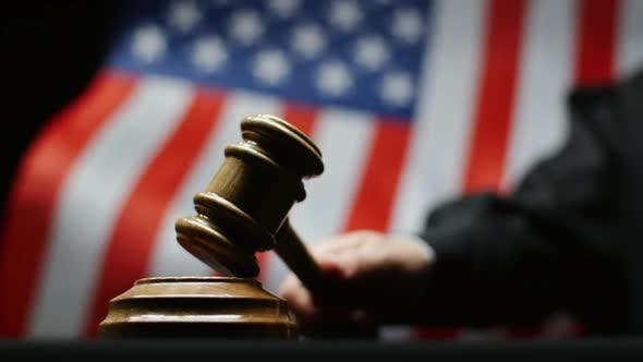 Thumbnail for Judge Hammering With Wooden Gavel Against Waving American Flag In USA Court Room