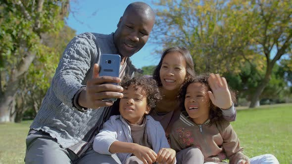 Thumbnail for Happy Interracial Family Waving and Having Video Chat on Smartphone