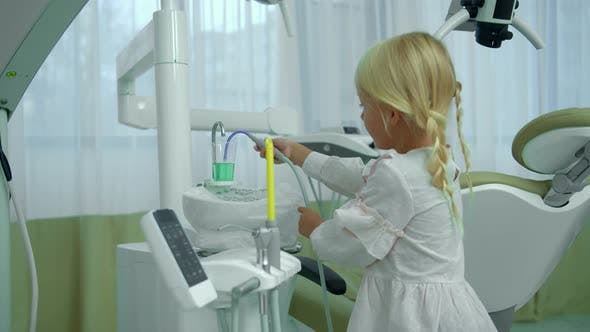 Thumbnail for Little Girl Checks Saliva Ejector in Cabinet