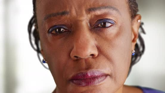 Thumbnail for A close-up of a elderly black woman looking sad