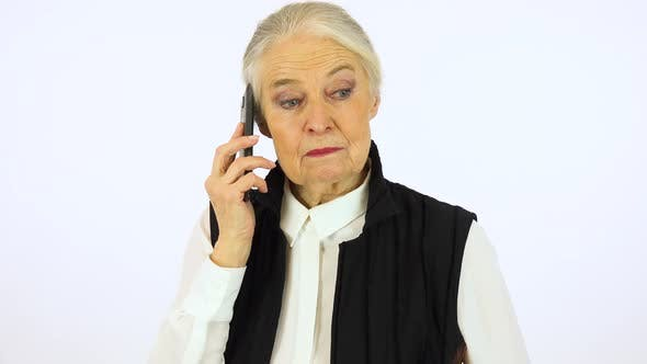 Thumbnail for An elderly woman talks on a smartphone with a smile - white screen studio