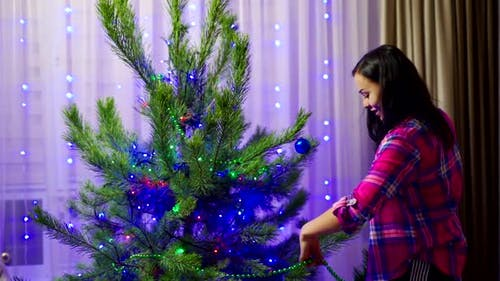 Girl Decorates Christmas Tree. Woman decorating Christmas tree in house