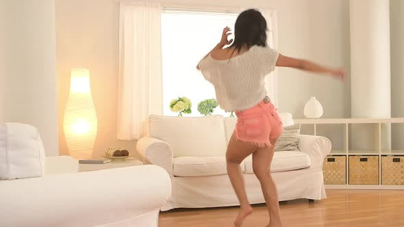 Thumbnail for Taiwanese woman jumping on couch and dancing in living room