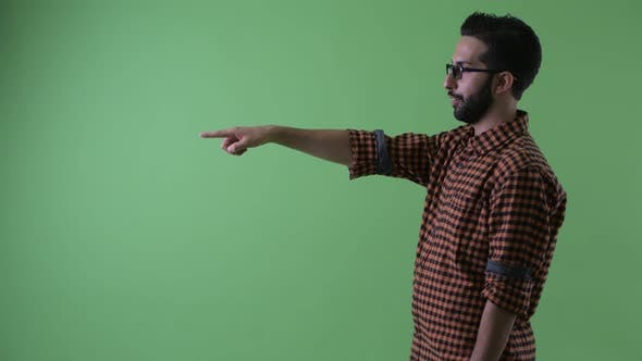 Cover Image for Profile View of Happy Young Bearded Persian Hipster Man Pointing Finger