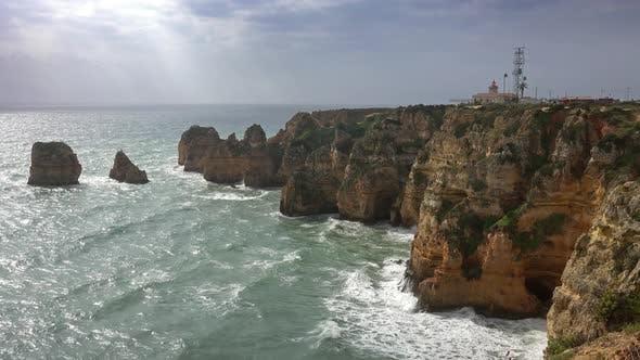 Leuchtturm auf Felsenklippen und Wellen in Portugal