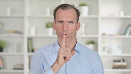 Portrait of Middle Aged Businessman Putting Finger on Lips