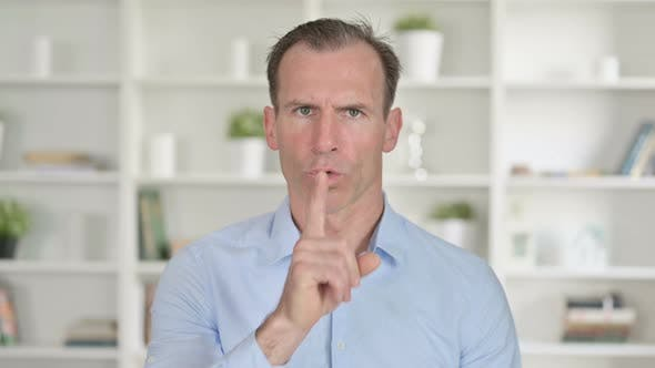 Thumbnail for Portrait of Middle Aged Businessman Putting Finger on Lips