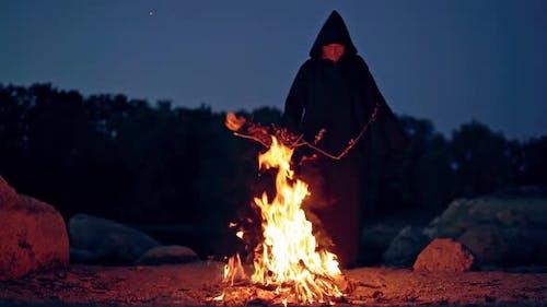 Hexe macht gruseliges Ritual im Feuer
