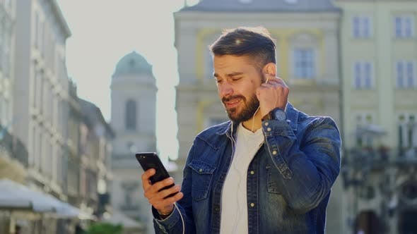 Thumbnail for Fröhlicher gutaussehender Bärtiger Mann in trendiger Jacke Hören Entzündliche Musik auf Kopfhörer und