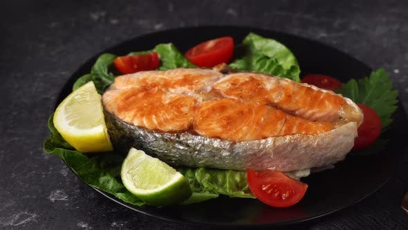 Grilled Salmon Steak with Salad Leaves in Ablack Plate