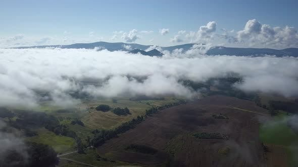 Thumbnail for Flying Above Clouds With Mountains In Back
