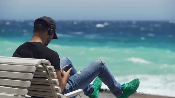 Thumbnail for Young Guy in Headphones Sitting on Bench by Ocean Coast, Typing Message on Phone