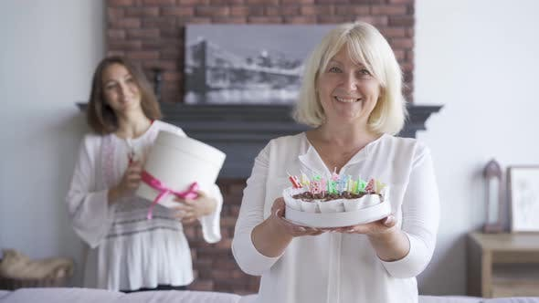 Thumbnail for Happy Senior Woman Showing a Cake To the Camera