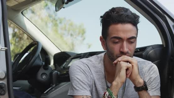 Thumbnail for Tired Hispanic man sitting in car smiling at camera