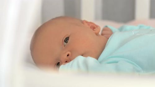 Newborn Baby Lying Quietly in Bed