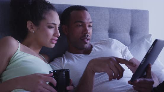 Thumbnail for Black and Hispanic couple sitting in bed using pad to browse internet together
