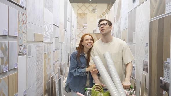 Schönes junges Paar wählen Wallpaper, Parkett und alles andere für zu Hause