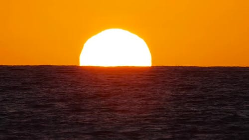 Big Red Hot Sun in Warm Air Distortion Above Ocean Horizon Sunset Over the Sea Big Rising Sun with