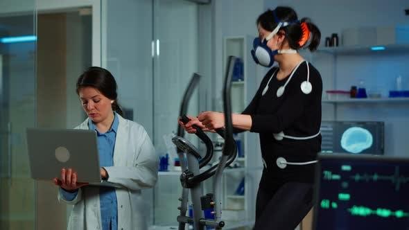 Medical Researcher Using Laptop While Measuring Sportsman Endurance
