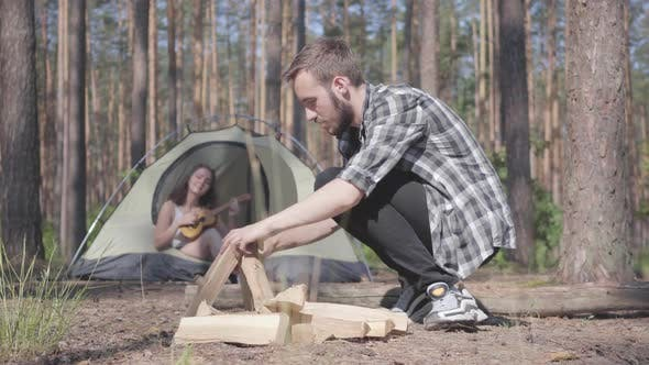 Cover Image for Portrait Handsome Man in a Plaid Shirt Prepares Firewood To Make a Fire Outdoors. The Girl Sits in a