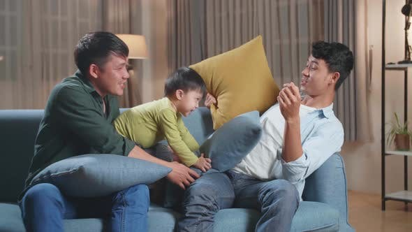 Happy Asian Gay Couple Having Fun With Their Lovely Son Fighting Pillows In Living Room
