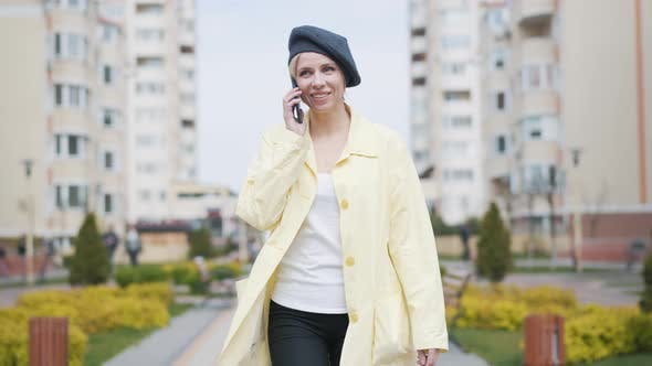 Thumbnail for Happy Positive Woman Walking Along the Alley in Residential Complex and Talking on the Phone