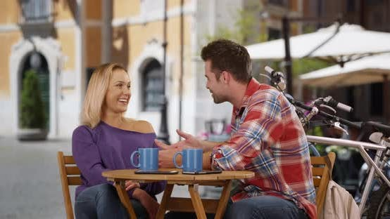 Thumbnail for Couple chatting and drinking coffee outdoors in Italy