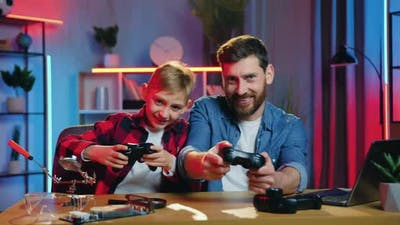 Bearded Dad and Teen Son Enjoying Videogames and Celebrating Victory