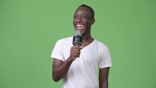 Young Happy African Man Smiling While Speaking on Microphone