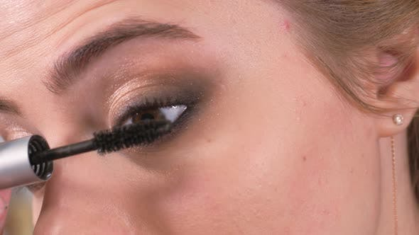 Thumbnail for Applying Makeup. Young Girl Looks in the Mirror and Applies Mascara with a Brush To the Lashes of