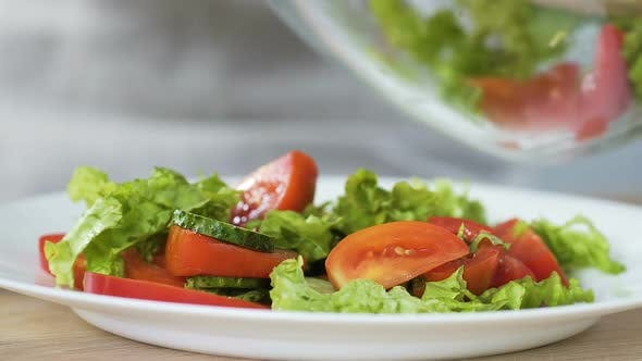 Thumbnail for Woman putting fresh vegetable salad from bowl to plate, healthy appetizer, detox
