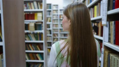 Woman Walking in Library Among Bookcases