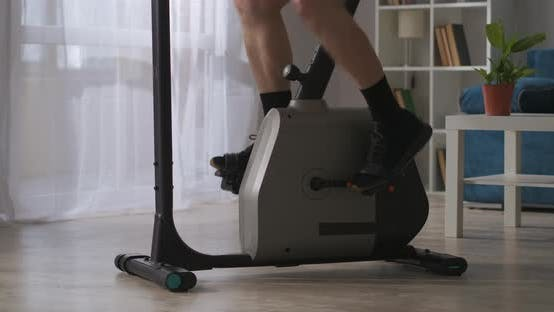 Thumbnail for Fitness in Home Man Is Spinning Pedals of Exercise Bicycle in Room Closeup View of Legs Healthy
