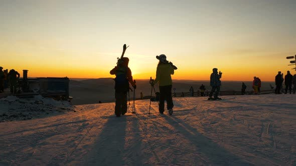 Silhouettes of People with Snowboards and Sticks on Slope