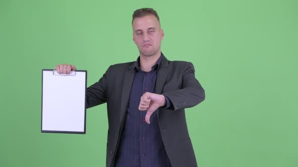 Thumbnail for Stressed Businessman in Suit Showing Clipboard and Giving Thumbs Down