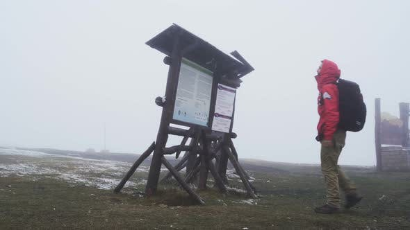 Thumbnail for Tourist in Red Jacket Reading and Checking Signs, Looking for Shelter From the Weather