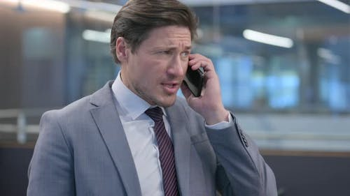 Portrait of Angry Middle Aged Businessman Talking on Smartphone