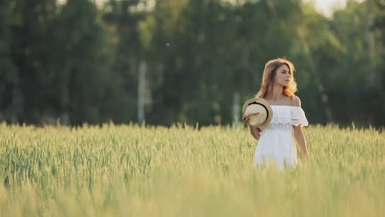 Girl with a Hat Walks in the Field