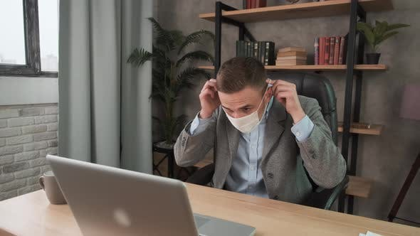 Young Businessman Wearing Protection Mask Face in the Office, Working Remotely at Home. Work During