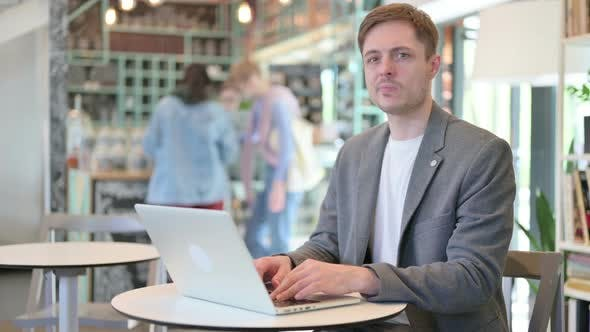 Thumbs Down By Young Man with Laptop in Cafe