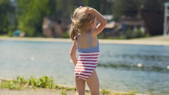 Close-up, Slow Motion: Little Girl in Bathing Suit Throws Stone at Lake, on Beach