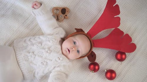 Six Month Old Baby Wearing Festive Christmas Reindeer Antlers.