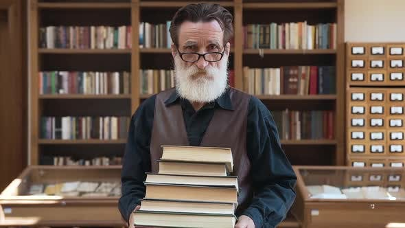 Thumbnail for Senior Bearded Man Holding a Lot of Books in His Hands and Posing on Camera