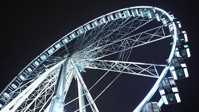 Brightly Lit Ferris Wheel Ride, Which Spinning at Night or Evening Carnival.