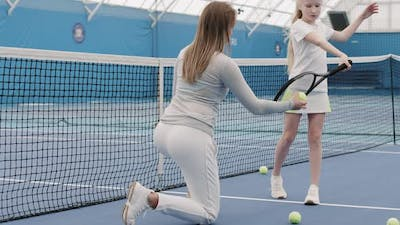 Girl Learning To Hit Tennis Ball On Court