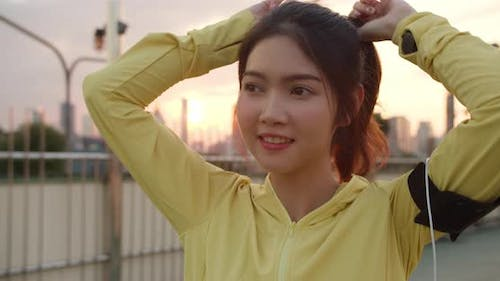 Happy young Asian athlete lady in yellow clothes preparing for training in urban environment