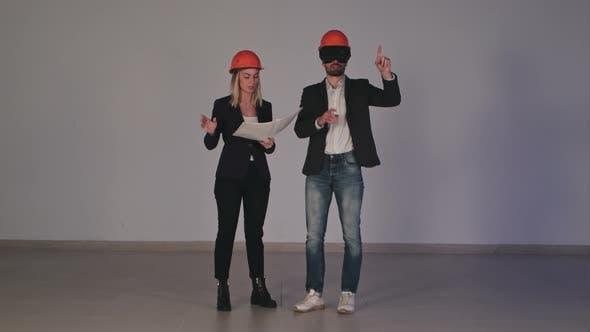 Thumbnail for Zwei Bauingenieure in Helmen mit VR Brille verwalten Bauprojekt in 3D