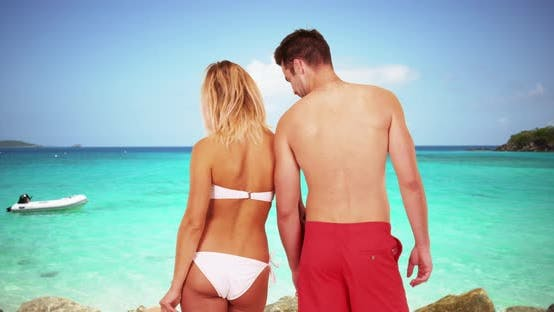 Thumbnail for Young attractive millennial couple standing together at the beach